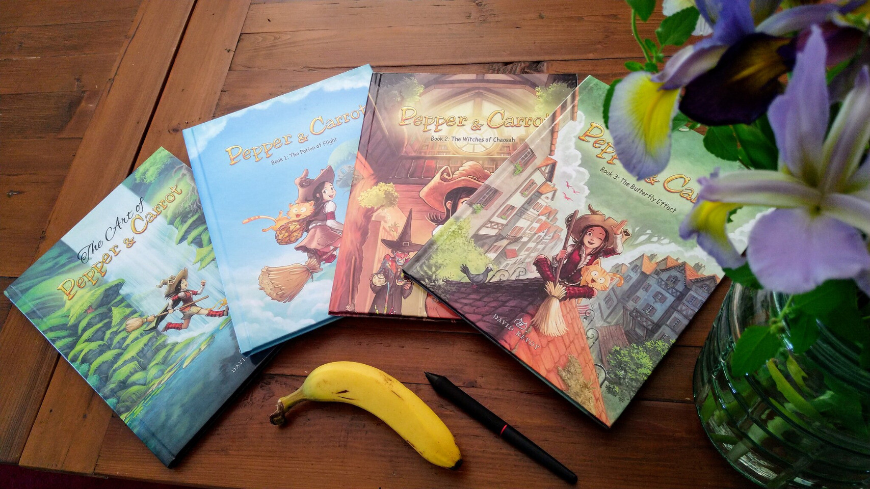 The 4 comic books on my table, a pot of flower in foreground, a banana and a stylus (for scale).